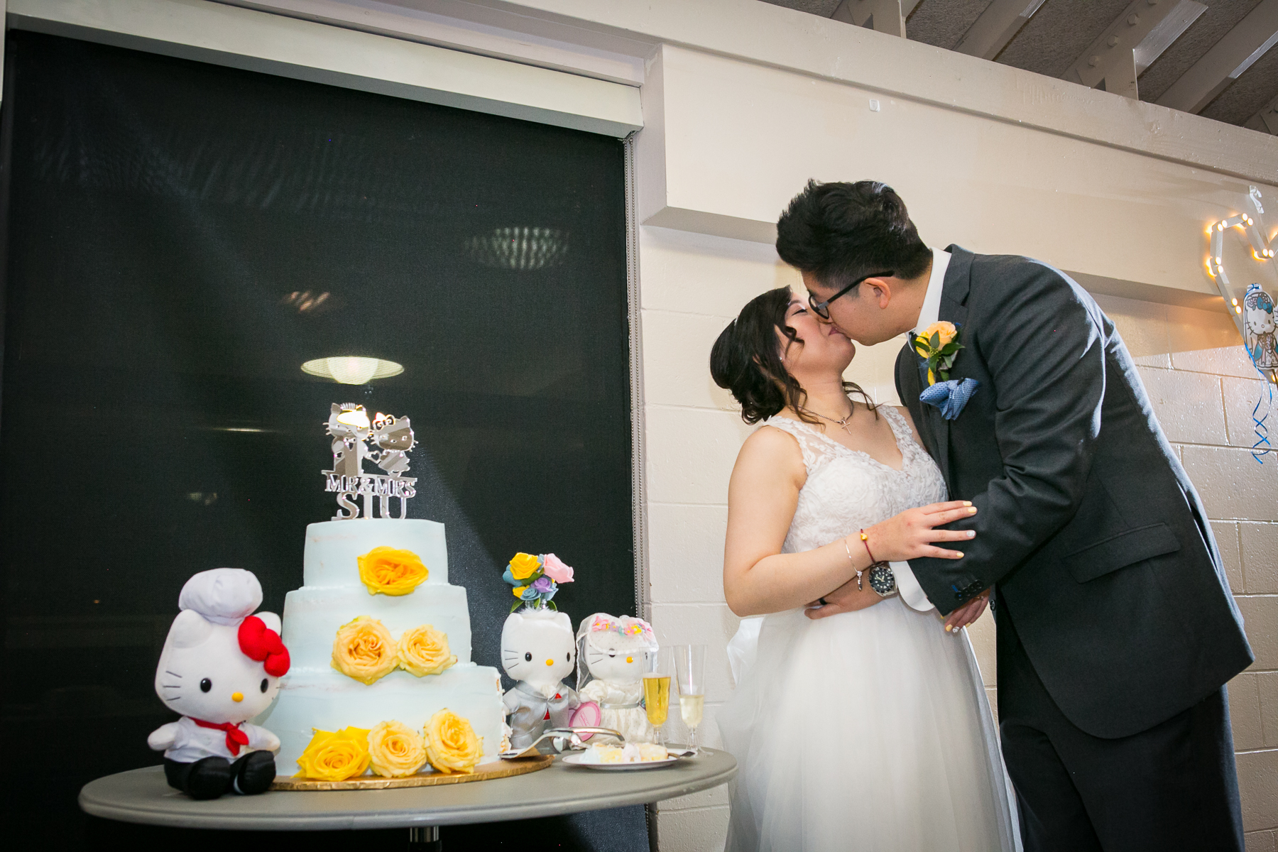 bride and groom kiss in front of cake at hello kitty cake at chino wedding photographer