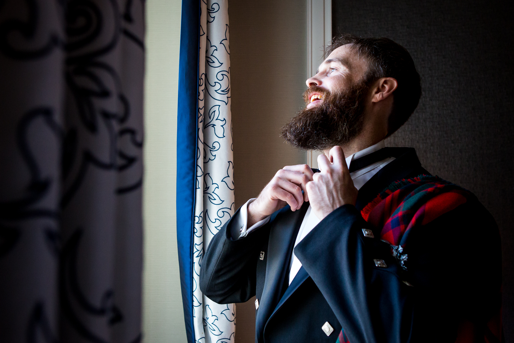groom smiles while looking out the window during wedding day in bay area