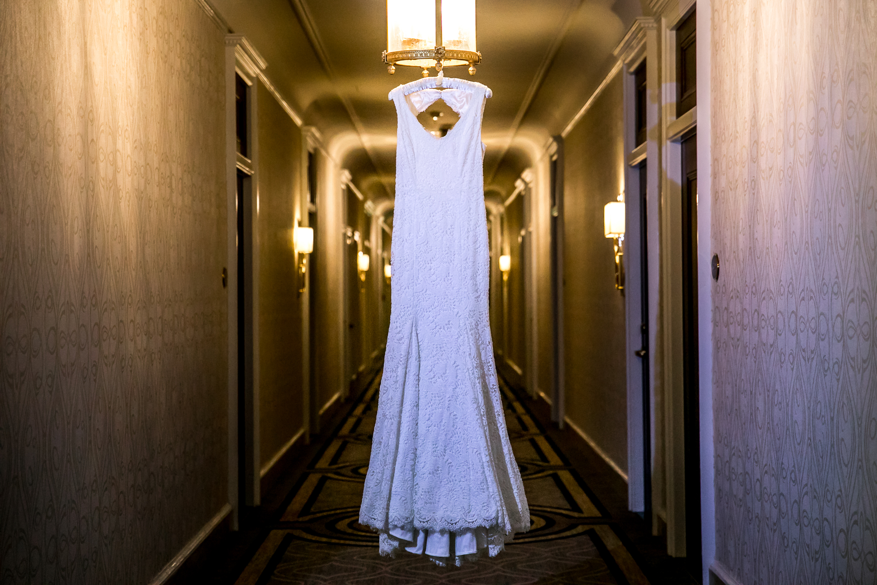 bride's wedding dress hanging in corridor bay area wedding photographer