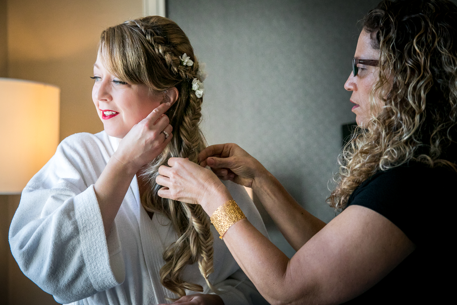 bride puts on earring at fairmont hotel wedding in san francisco