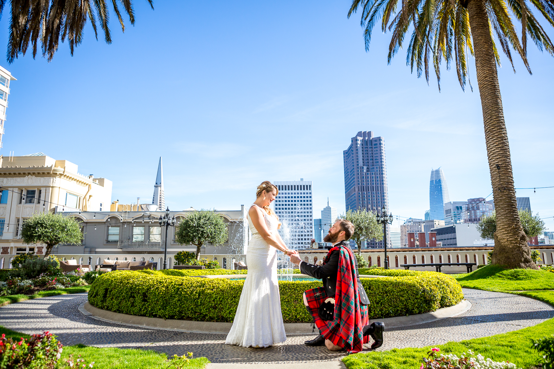 scottish groom on one knee on rooftop garden wedding at fairmont hotel in san francisco wedding photographer