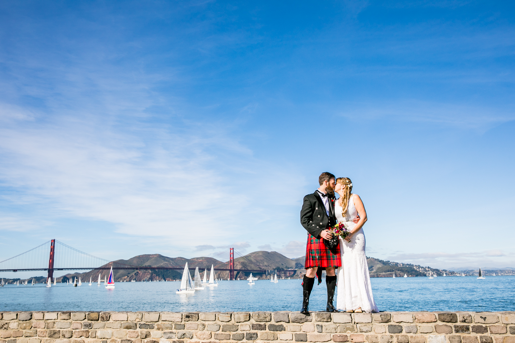 wide shot of golden gate bridge with bride and groom